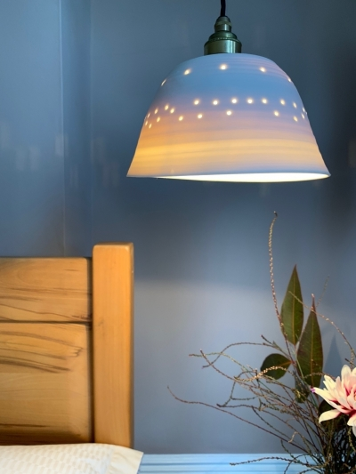 This pretty porcelain pendant lamp by ceramicist Jacqui Roche creates a lovely luminous bedside ambience.